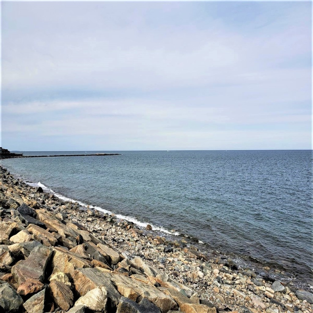 Ocean View from Brant Rock. Rock revetment in the foreground and blue ocean and light sky in the background.