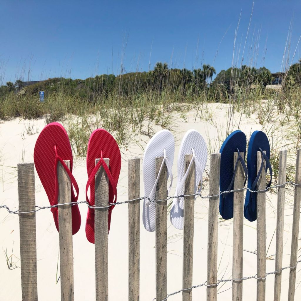 Red, white and blue flip flops on a dune fence. Sand and green trees in the background.