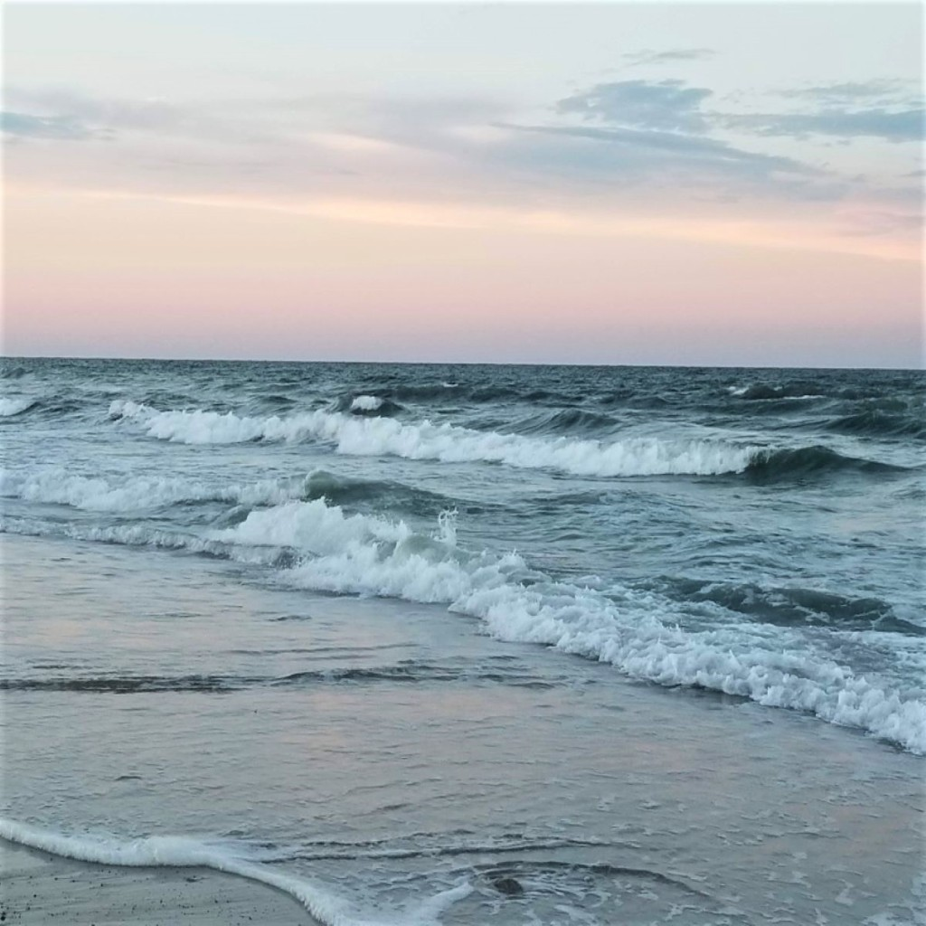 Dark blue ocean waves with white foam pink and light blue sky.